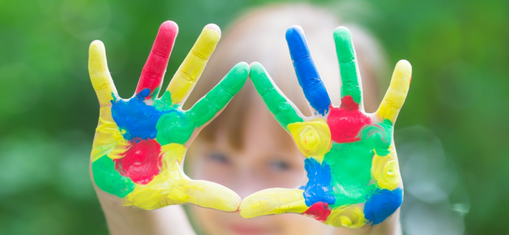 a child's hands painted with yellow, blue, red and green paint